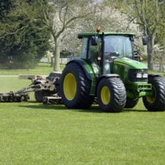 A gardener trims the grass with the aid of a large John Deere. | Richard Brockbank