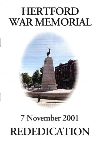 Words HERTFORD WAR MEMORIAL above a vertical ellipse showing a photograph of the war memorial with blue sky background with the words 7 November 2001 REDEDICATION beneath | Hertford Town Council