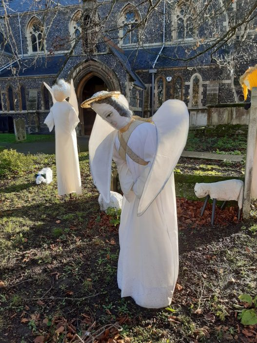 Close up of a white angel looking down at baby Jesus | Gill Cordingley