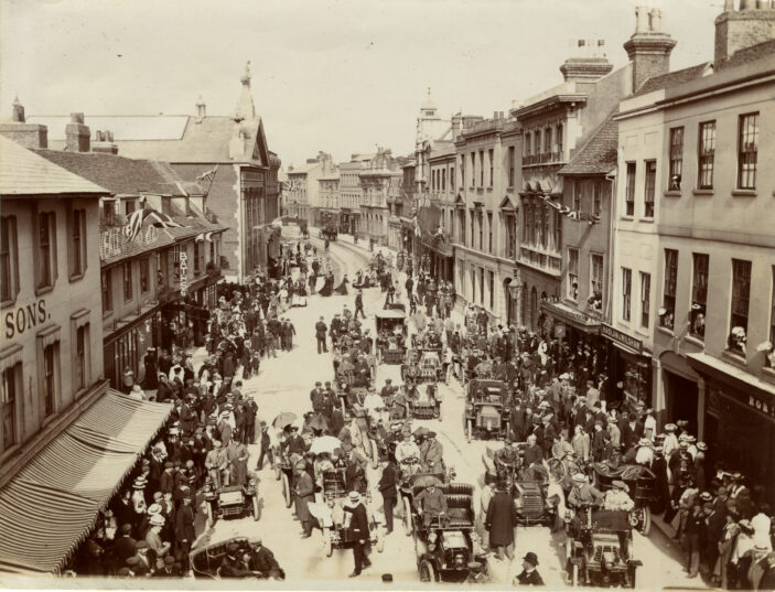 Motor cars lined up in town street with many onlookers   HALS