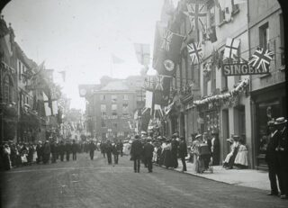 Photograph of crowds lining the street in anticipation of a Royal visit