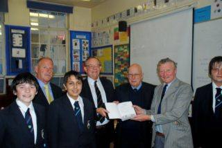 Three of the boys presenting a Remembrance Book to Peter Ruffles. Other adults in the picture are from left to right the Headmaster Mr Stephen Neate, Mr Richard Creese whose uncle is featured in the Book, and Mr Eddie Roche, the Curator of the Old Pupils' Heritage Room.