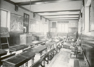 The interior of the Old Grammar School, showing the single long room in which all the teaching was done. A portrait of the founder, Richard Hale, can be seen above the door on the left