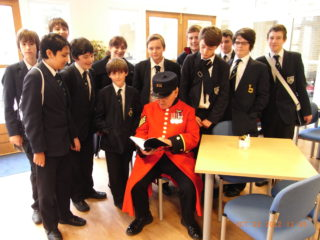 Junior History Club boys, and teacher Lyndsey Matthews, taken at Chelsea Hospital with one of the Chelsea Pensioners.