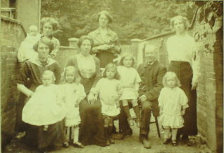 Family photograph with Rene on right and her father sat next to her?