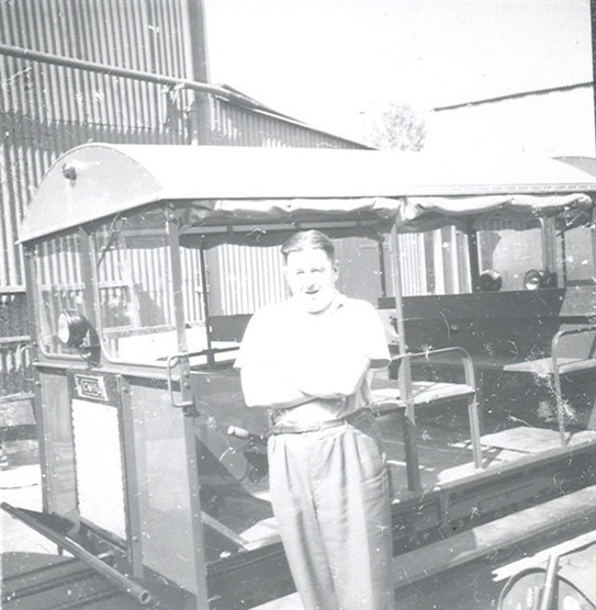 A worker standing in front of a railcar